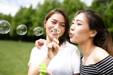 Cute asian girlfriends making soap bubbles in the park.