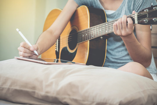 Female musicians play guitar and write songs using the tablet.This image is blurred and soft focus.