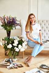 Beautiful sexy blonde woman sits on the sofa in the restroom looks family album with photo of memories of friend bright room flower,sofa,cozy family hearth, model wear white t-shirt and blue trousers.