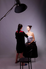 Backstage of photo session. Makeup artist doing makeup for woman / girl / female in studio