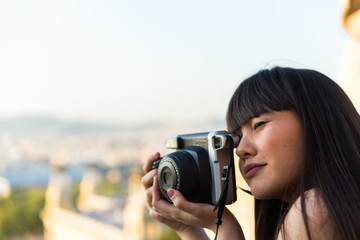 Eurasian woman with a vintage polaroid camera in Barcelona