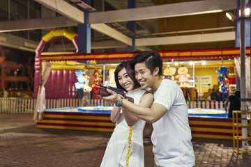 Beautiful couple having fun at a carnival in Singapore