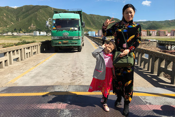 With the North Korea in the background, people pose on the red line marking the border in Tumen