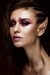 Brunette girl with a creative hairstyle braids, art make-up and the elf's ears. Beauty face. Photo taken in the studio.