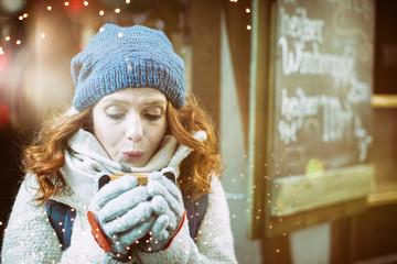 hübsche Frau auf dem Weihnachtsmarkt mit heissem Getränk