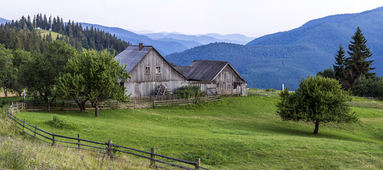 Keuken foto achterwand Heuvel Village houses on hills with green meadows in summer day. House of shepherds in mountains in carpathian