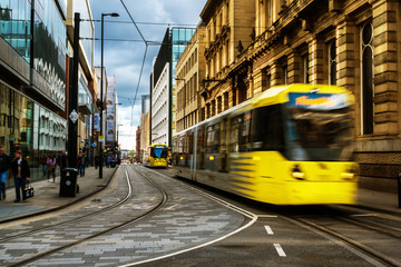 Light rail yellow tram in the city center of Manchester, UK