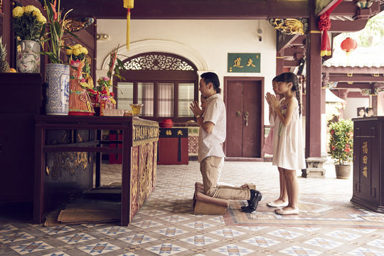 Family praying in Asian temple