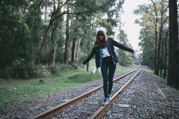 Young single woman walking on railway tracks in Australia