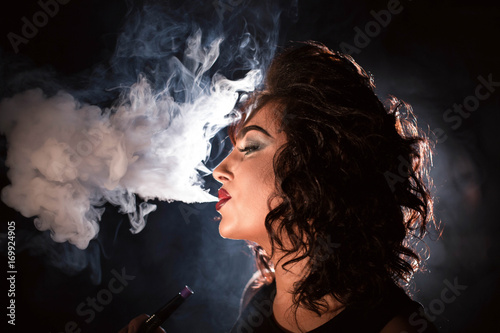 Portrait of woman with her eyes closed and exhaling hookah