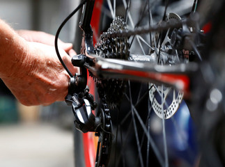 A mechanic adjusts a gear shift of a KTM bicycle in a garage in Vienna