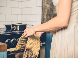 Woman in kitchen with burnt cake and oven gloves