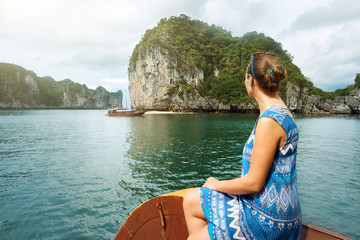 woman in dress is traveling by boat among the islands in Halong Bay. Vietnam.