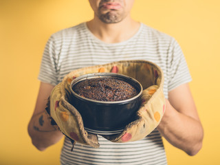 Upset young man with burnt cake