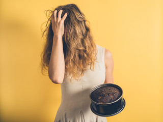Woman with burnt cake pulling her hair
