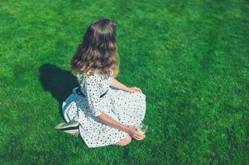 Woman in dress sitting on lawn in summer