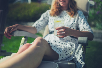 Woman drinking from glass in deck chair