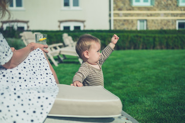 Mother with baby relaxing on deck chair in garden