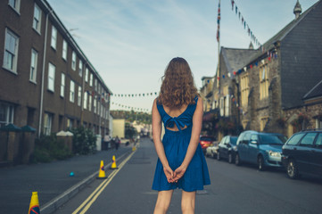 Woman in blue dress standing in the street