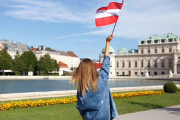 Young woman showing austrian flag in park