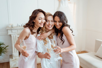 bride with bridesmaids embracing and toasting