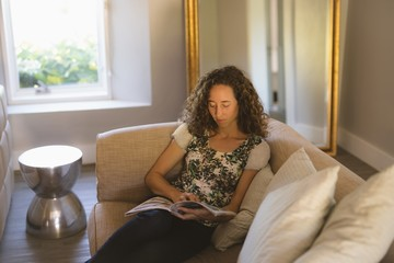 Woman reading book while relaxing on sofa