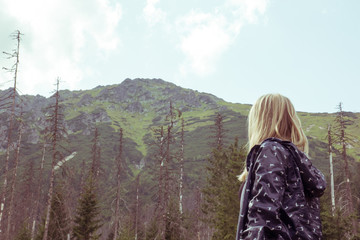 The blonde looks at the mountains