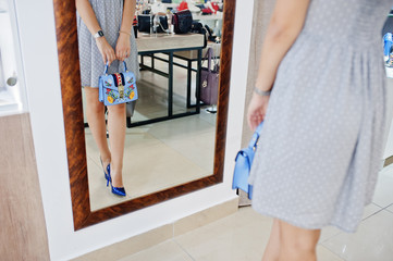 Portrait of a fantastic young woman in grey dress trying on new shoes and handbag in front of a mirror in shop.