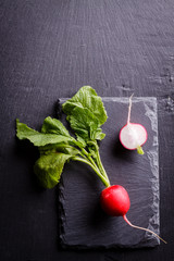 Top view of fresh radish lay on black slate plate.