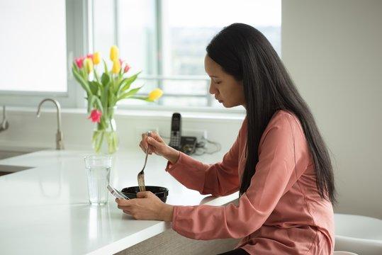 Woman having breakfast in living room
