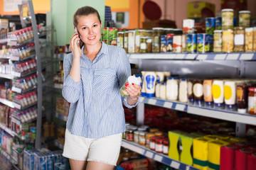 Woman 25-35 years old is talking phone and choosing mushrooms