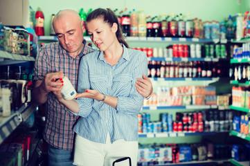 Adults woman and man choosing mayonnaise at the modern supermarket