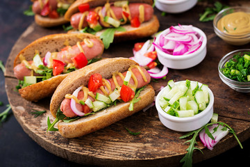 Hot dog with cucumber, tomato and red onion on wooden background.