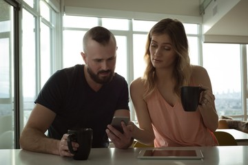 Couple using smartphone while having coffee at home