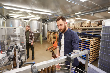 men with bottles on conveyor at craft beer brewery
