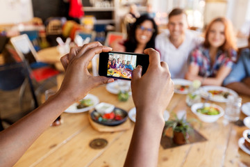 friends taking picture by smartphone at restaurant