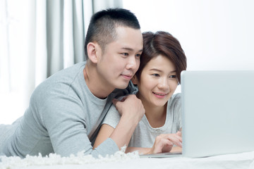 Loving Asian couple using a laptop