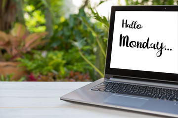 Monday text wrote on screen laptop over wood table with green garden background