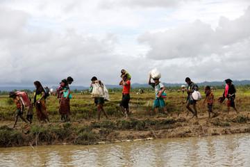 A group of Rohingya refugee people walk towards Bangladesh after crossing the Bangladesh-Myanmar border in Teknaf