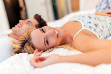 Beautiful couple lying on bed and smiling