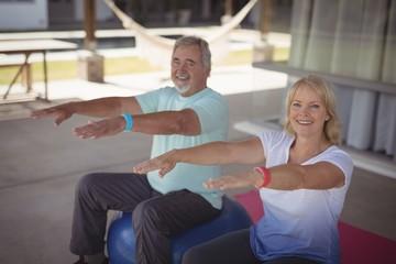 Smiling senior couple exercising on exercise ball