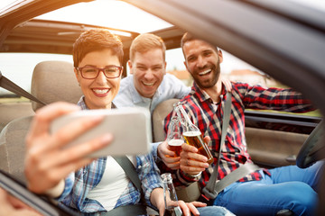 leisure, road trip, travel and people concept - friends driving in cabriolet taking selfie by smartphone.