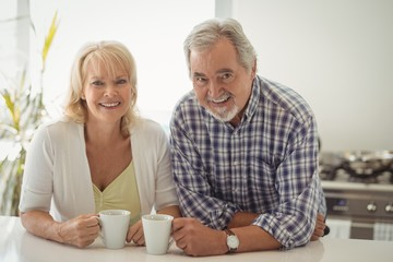 Senior couple holding coffee cup