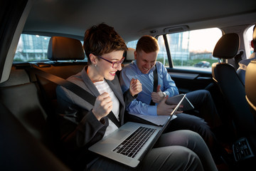 Businesspeople looking at laptop in car on trip.