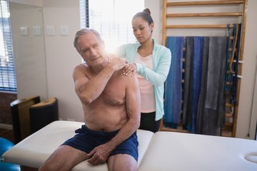 Shirtless senior male patient sitting on bed receiving neck