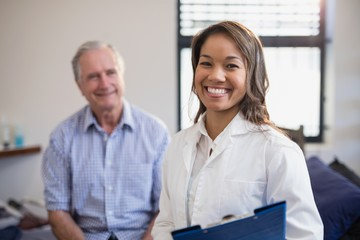 Portrait of smiling female therapist holding file with senior