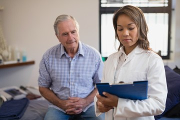 Senior male patient and female therapist looking at file