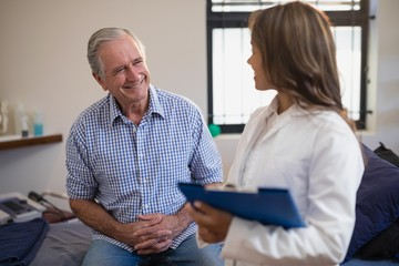 Smiling senior male patient looking at female therapist with