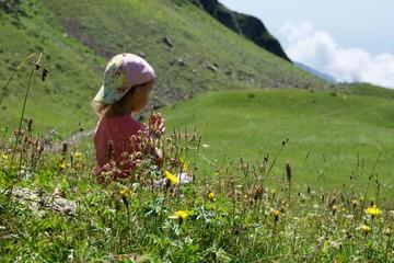 Little cute girl meditating in mountain landscape.