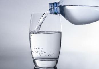 Wasserglas mit Wasser aus der Flasche füllen- Trinkwasser